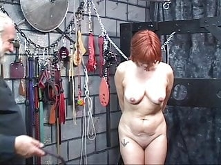 Redhead brunette milf gets whipped in the dungeon by older bearded man
